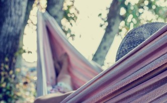 Vintage toned image with an instagram effect of a woman relaxing on a hot summer day in a hammock strung in the shade of a tree.