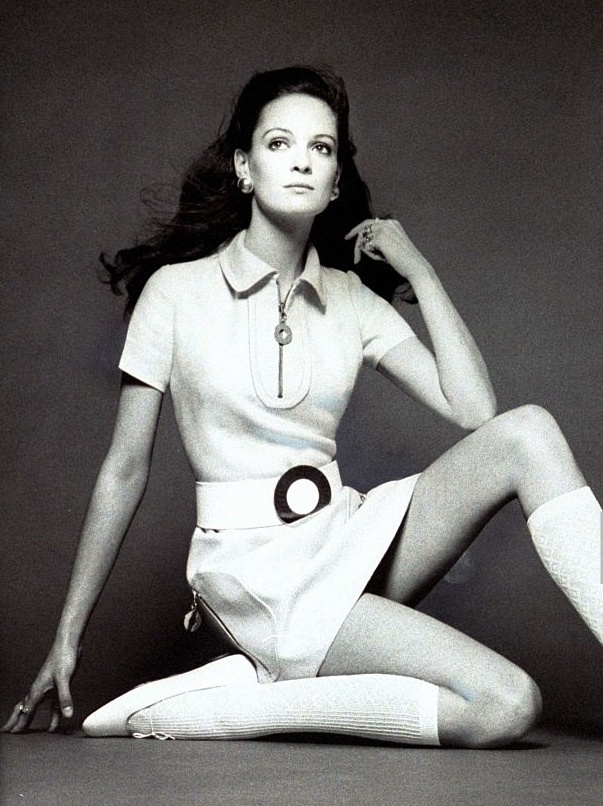 Martha Laycock wearing short-sleeved white linen shirtdress with collar zipper, U-shaped placket, and curved, zippered patch pockets at the hips, designed by Elio Berhanyer; wide white leather belt with huge circular buckle; white ribbed kneesocks and slippers; earrings; coiffure by Marc Sinclaire of Charles of the Ritz *** Local Caption *** Martha Laycock;